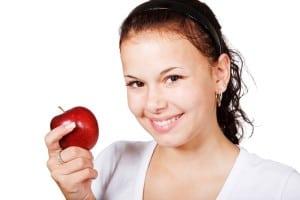 Frau hält roten Apfel und lächelt